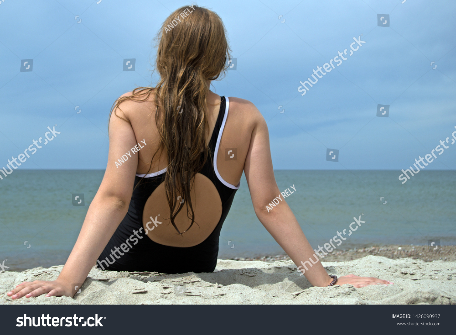 A girl in a black one-piece swimsuit, sitting on a sandy beach with her back to the viewer, looking into the distance