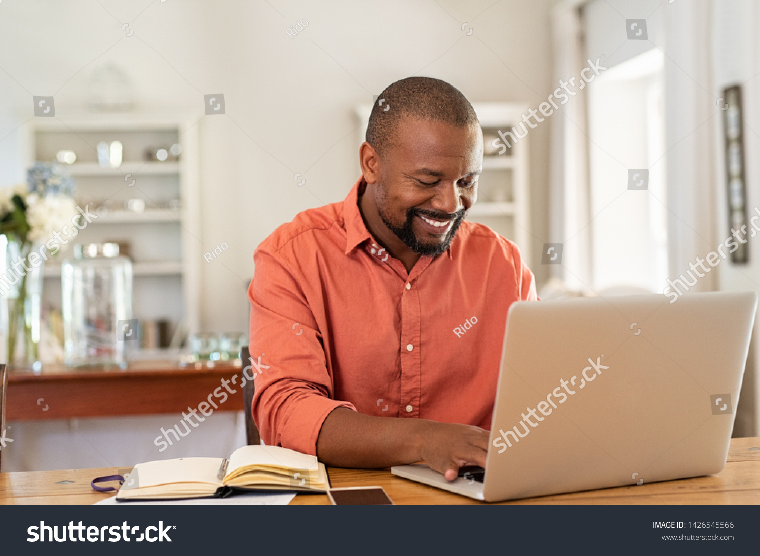 Smiling black man using laptop at home in living room. Happy mature businessman send email and working at home. African american freelancer typing on computer with paperworks and documents on table. #1426545566