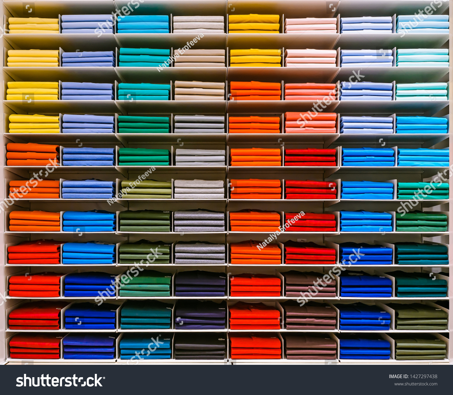 Colorful rainbow clothes background .Various vibrant color shirts perfectly folded on a shelf in the shop. Colored male clothes displayed in store. T-shirt of different color are neatly stacked in a #1427297438