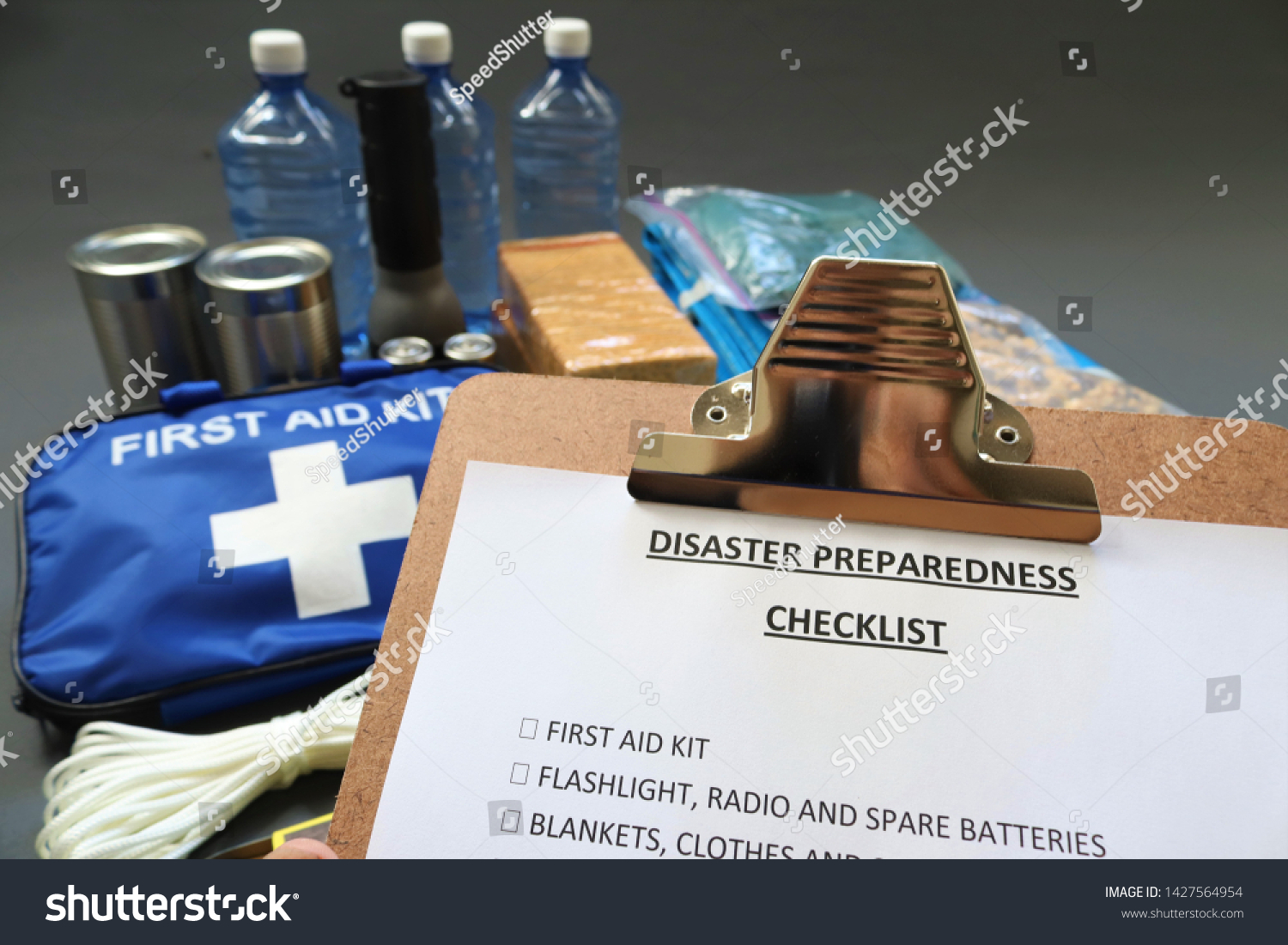 Disaster preparedness checklist on a clipboard with disaster relief items in the background.Such items would include a first aid kit,flashlight,tinned food,water,batteries and shelter.Disaster plan. #1427564954