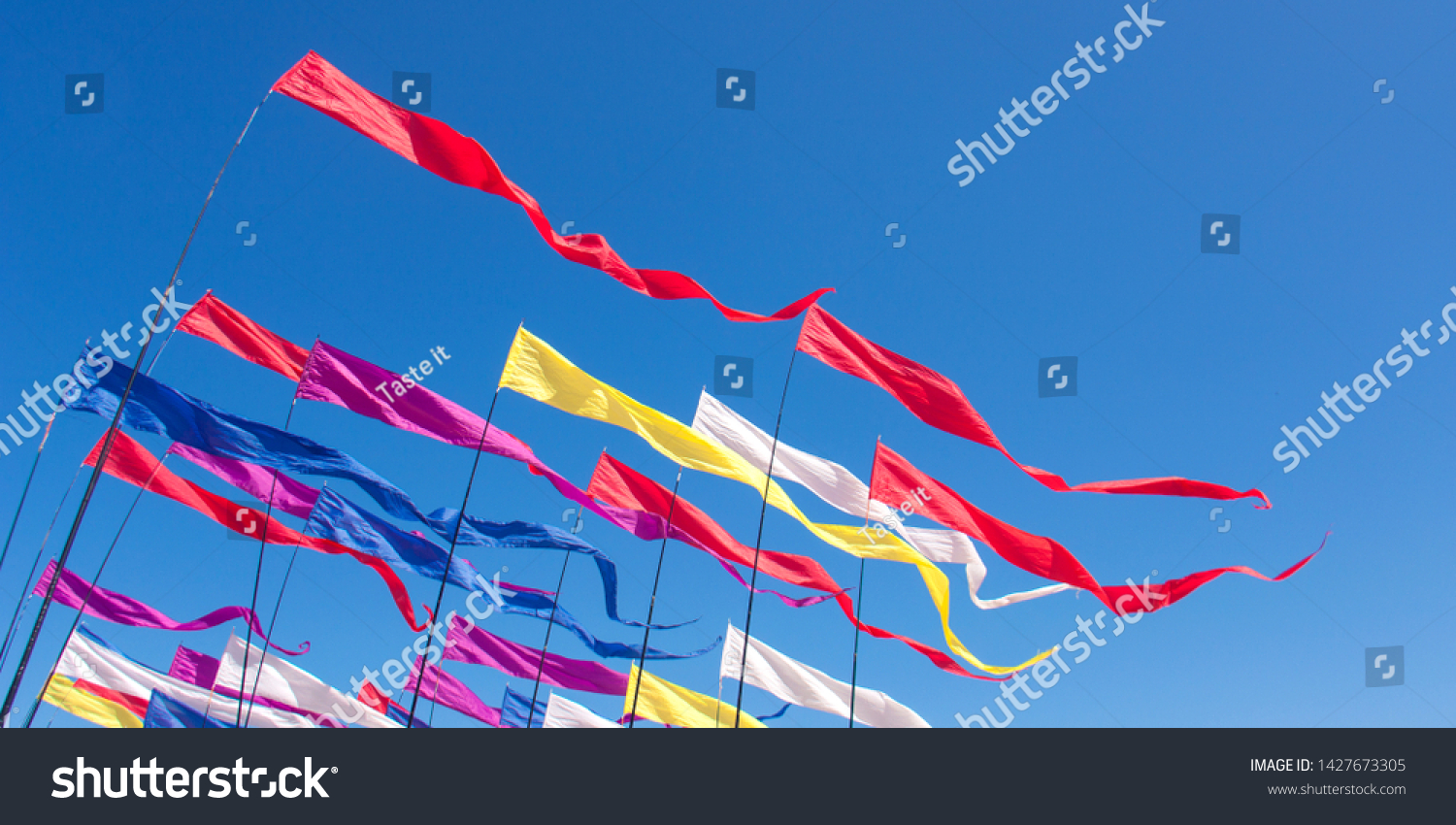 Multicolored kites in the form of bright ribbons on pillars, fluttering in the blue sunny sky in windy weather. Banner #1427673305
