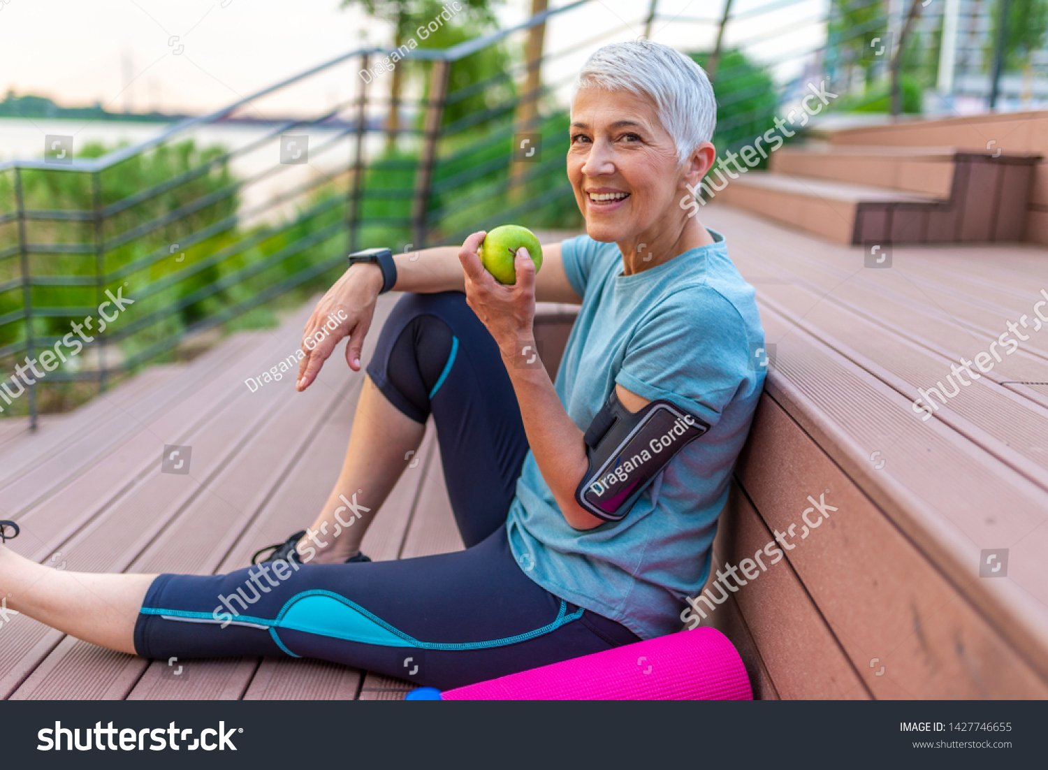 Sporty woman eating apple. Beautiful woman with gray hair in the early sixties relaxing after sport training. Healthy Age. Mature athletic woman eating an apple after sports training  #1427746655