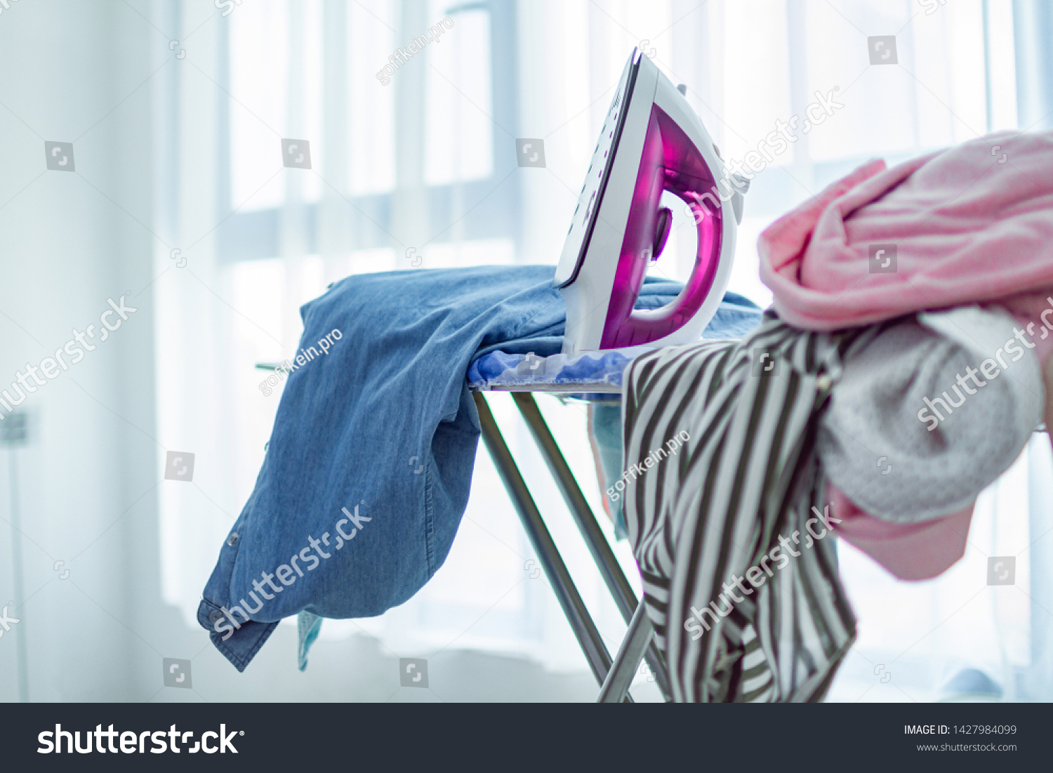 Iron and pile of clean clothes after laundry on ironing board  #1427984099