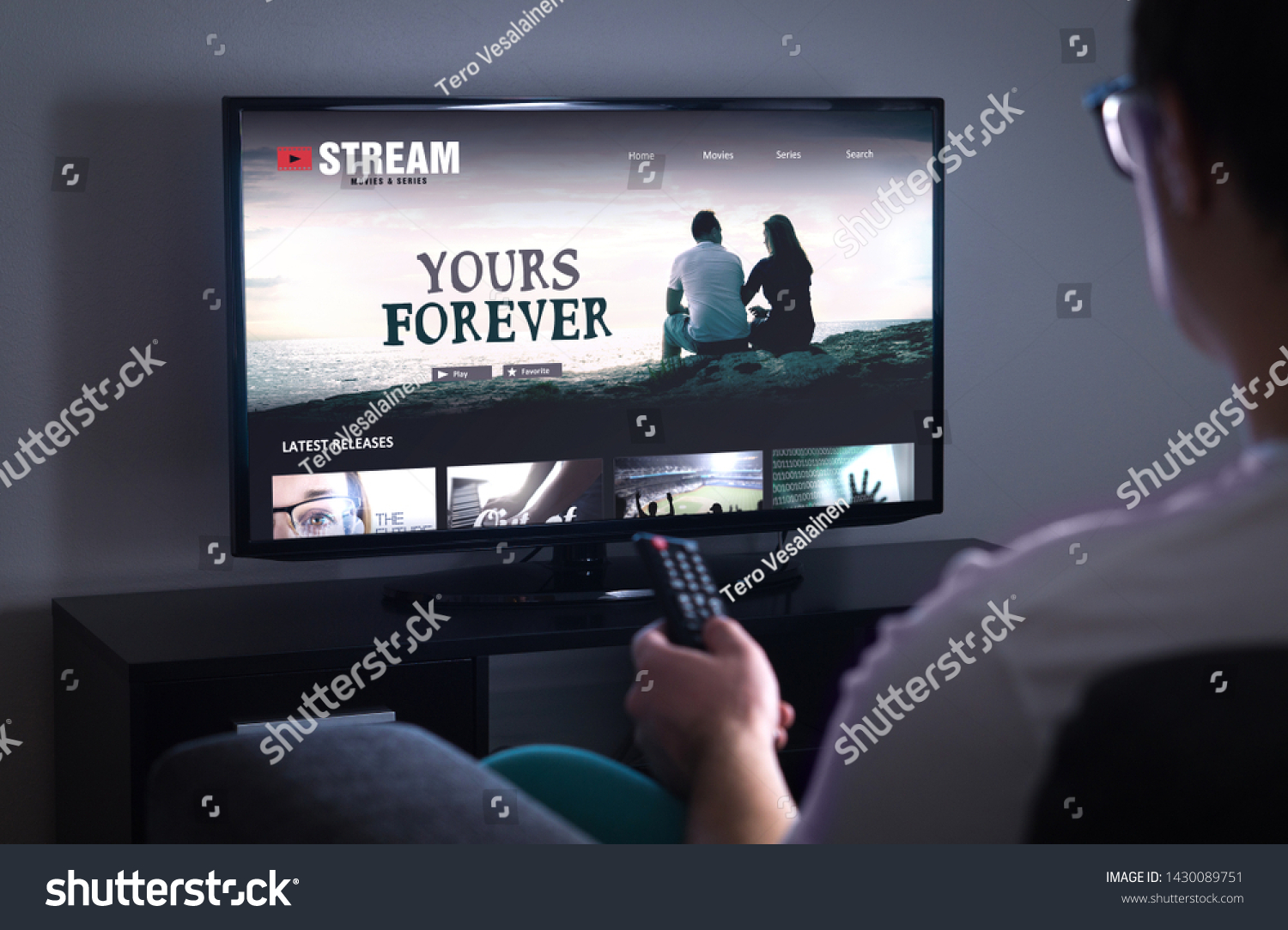 Online movie stream service in smart tv. Streaming series with on demand video (VOD) service in television. Man choosing film to watch with remote. Person sitting on couch at home late at night.