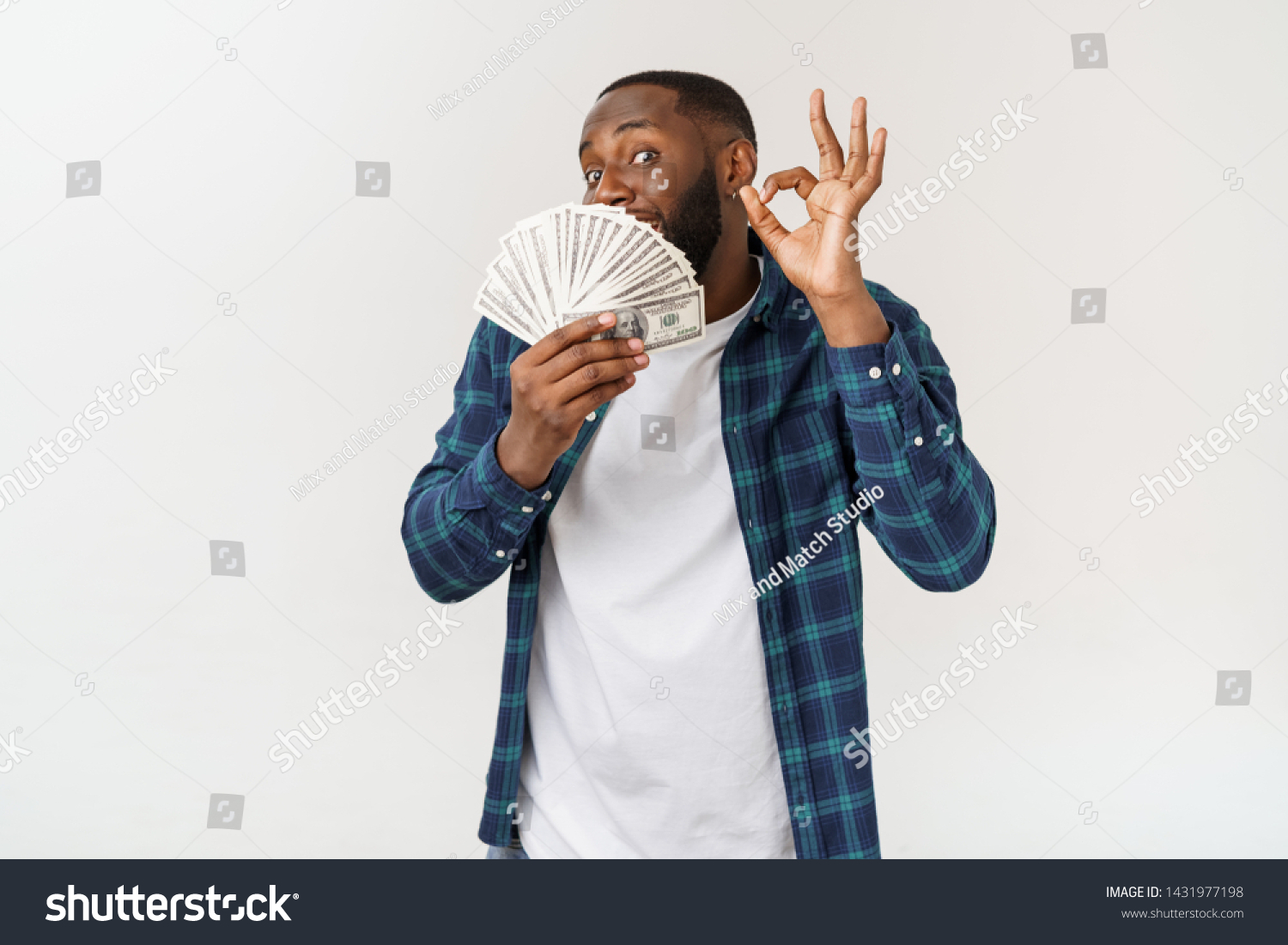 Portrait of young smiling dark skin african american man in white t shirt holding money and showing okay sign isolated on gray background #1431977198