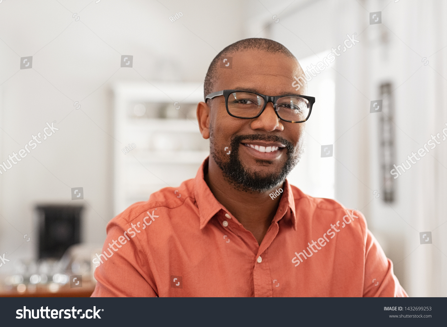 Smiling mature man wearing spectacles looking at camera. Portrait of black confident man at home. Successful entrepreneur feeling satisfied. #1432699253