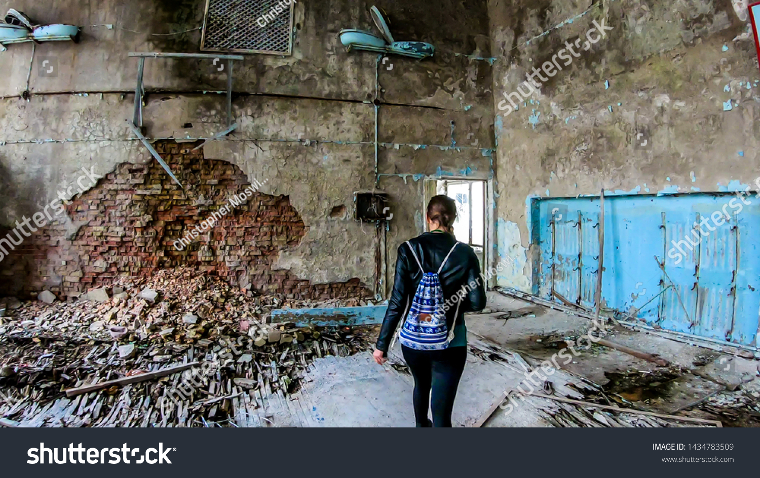 Girl in black outfit walks around the rotten floor in an abandoned sports hall in Pripyat, Ukraine, after the Chernobyl explosion. The floor is completely rotten. Lots of decaying object on the floor #1434783509