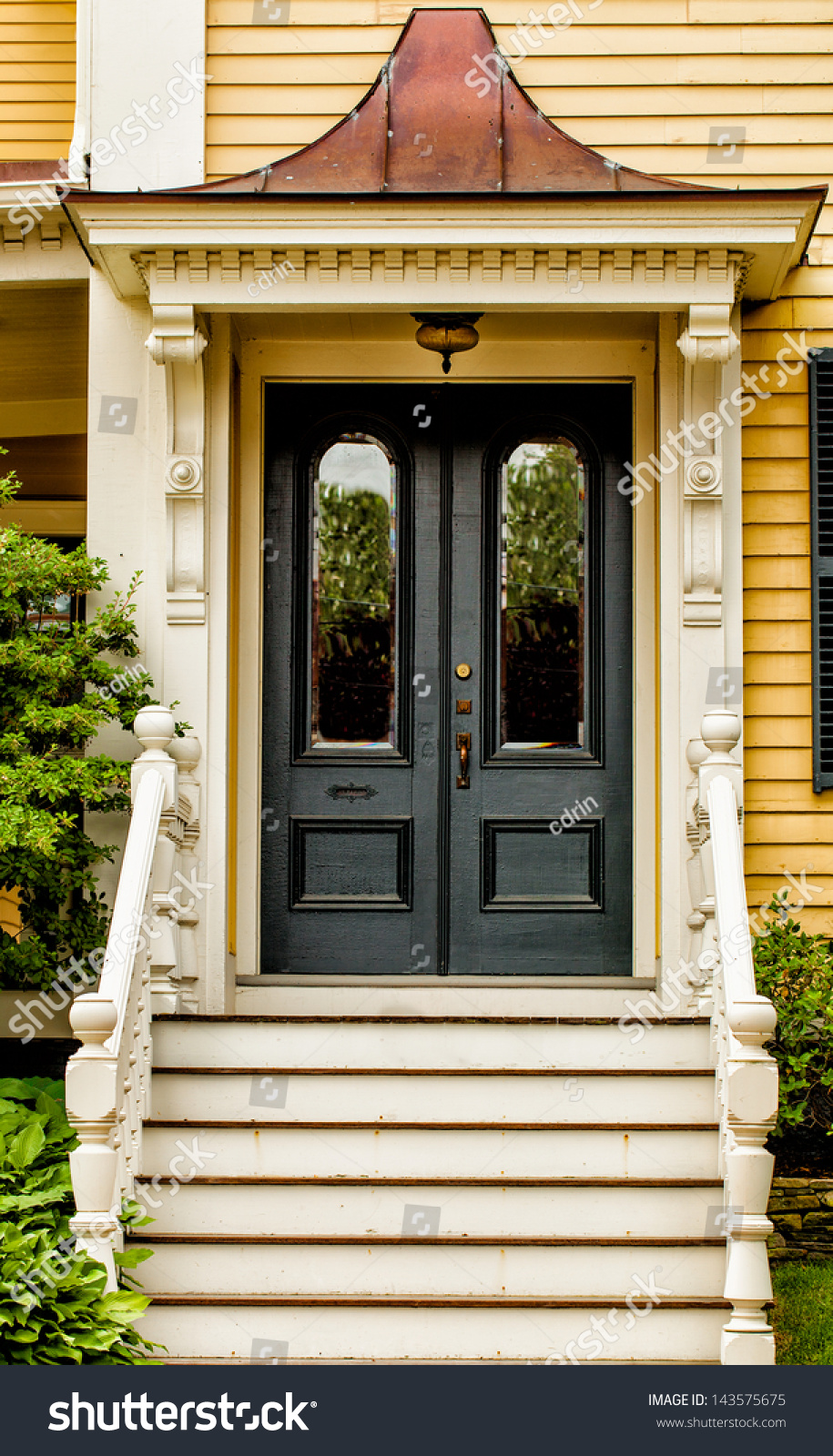 Front Door Of A Vintage Yellow House With White Trim And A