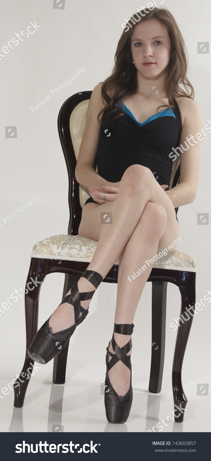Teen Ballerina Sitting In A Chair With Her Legs Crossed In A Ballet Leotard And Pointe