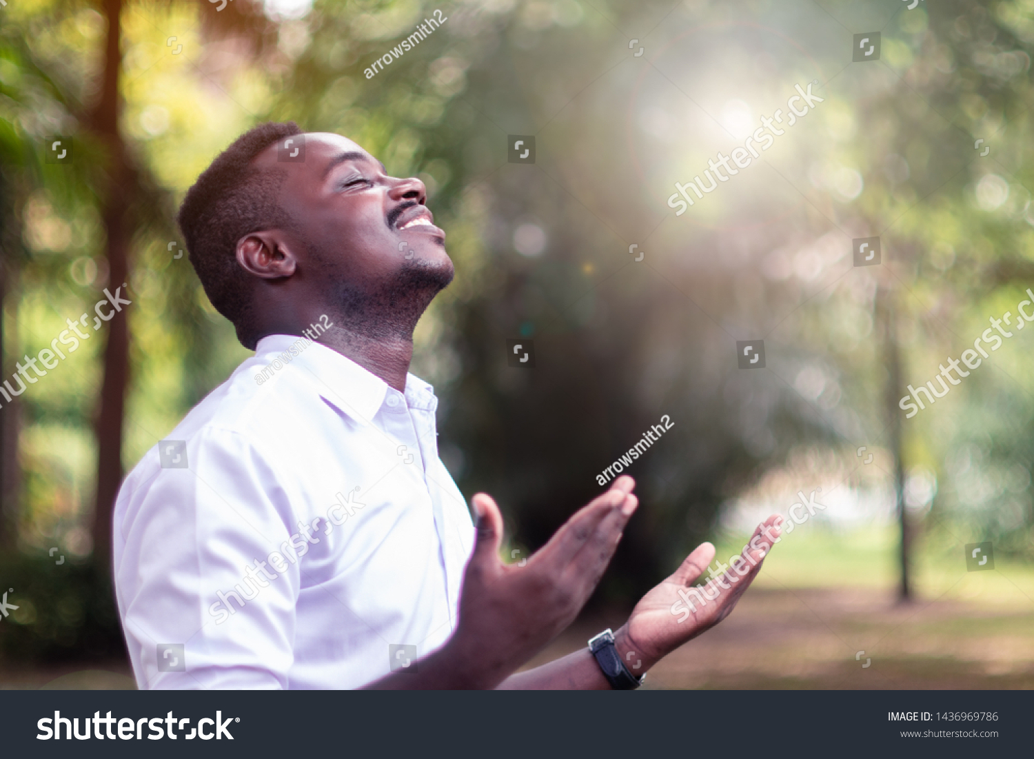 African man praying for thank god with light flare in the green nature #1436969786