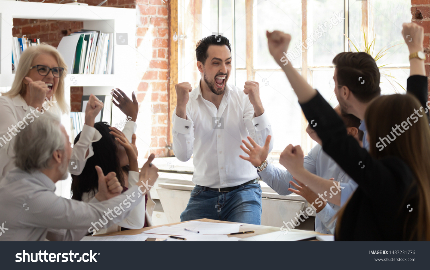Euphoric excited business team celebrate corporate victory together in office, happy overjoyed professionals group rejoice company victory, teamwork success win triumph concept at conference table #1437231776