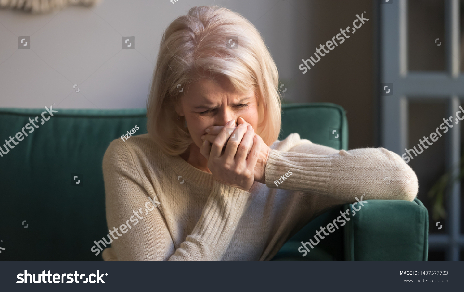 Sad stressed old middle aged woman widow mourning crying alone sit on couch at home, upset desperate senior mature elder grandma grieving weeping suffering from anxiety grief sorrow disease concept #1437577733