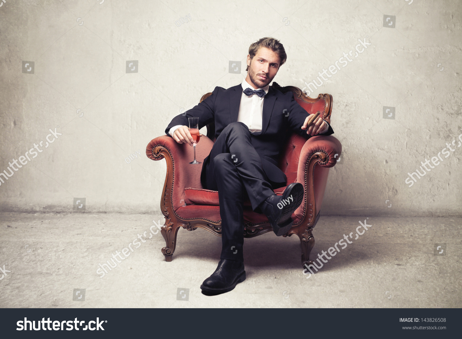 Attractive young man sitting on an armchair stock photo for Sitting in armchair
