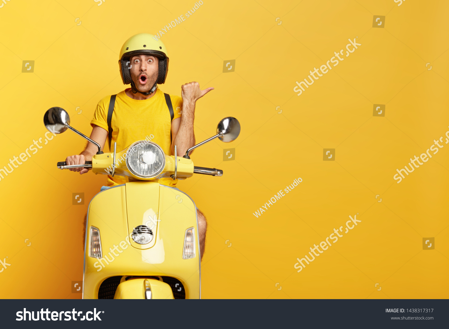 Impressed driver covers distance on yellow motorbike, wears helmet, indicates with great wonder aside, stops on road, demonstrates blank space for your advertising content, tries new vehicle. #1438317317
