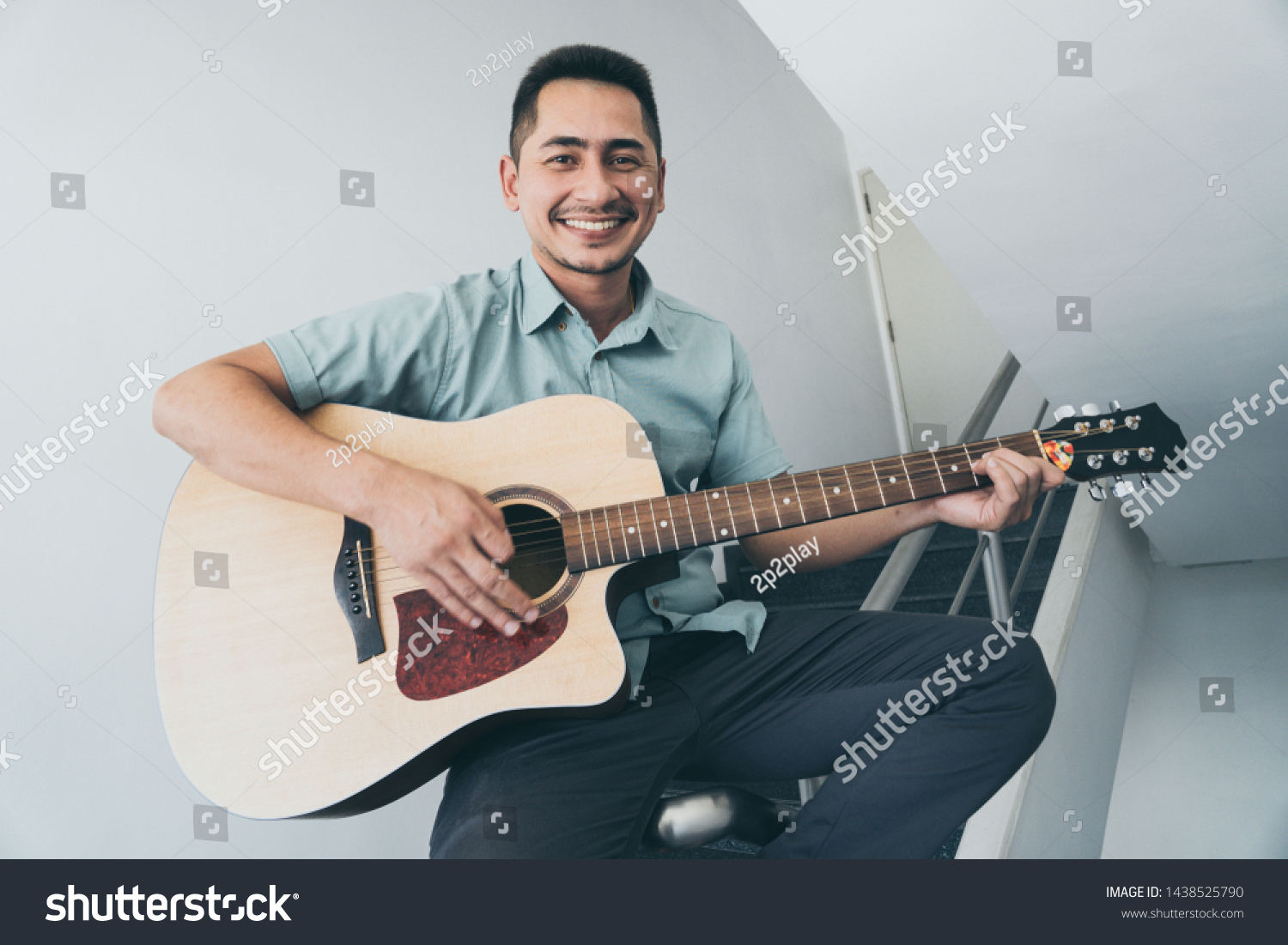 Cheerful guitarist. Cheerful handsome young man playing guitar and smiling while sitting on banister, process color and effect grain. #1438525790