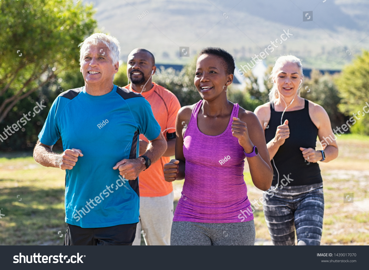 Healthy group of mature people jogging on track at park. Happy senior couple running at park with african friends. Multiethnic middle aged friends exercising together outdoor. #1439017070