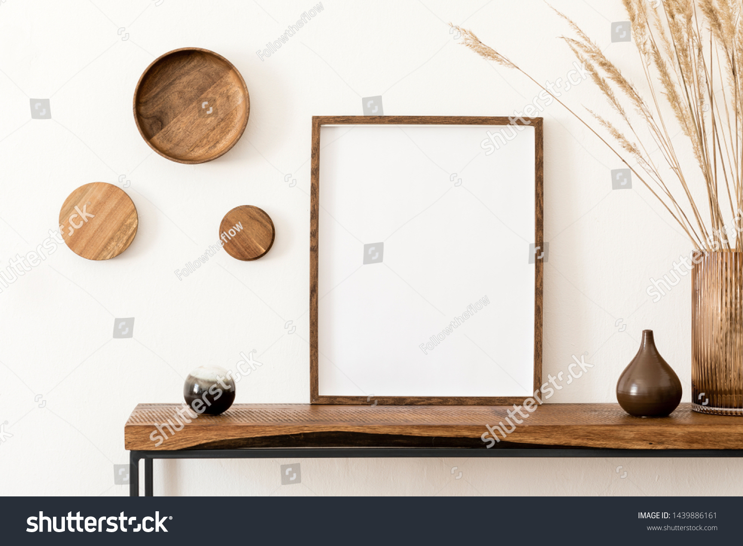 Design scandinavian interior of living room with wooden console, rings on the wall, mock up poster frame, flowers in vase and elegant personal accessories. Modern home decor. Template. #1439886161