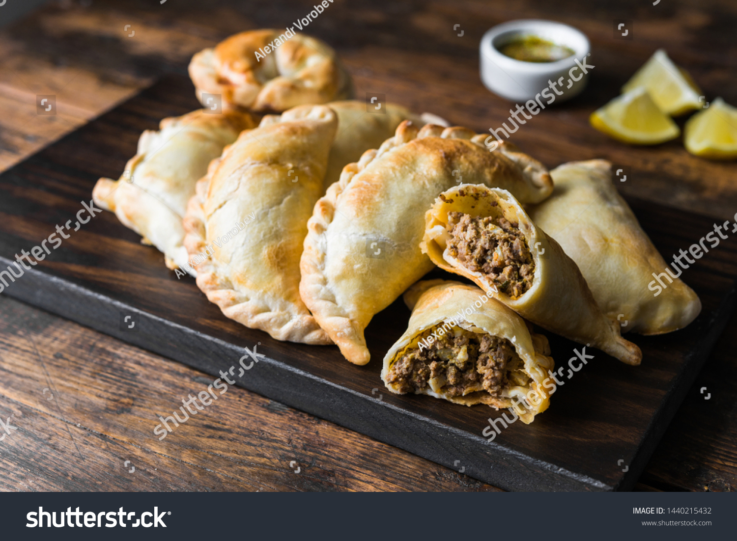 Traditional baked Argentine empanadas savoury pastries with meat beef stuffing against wooden background #1440215432
