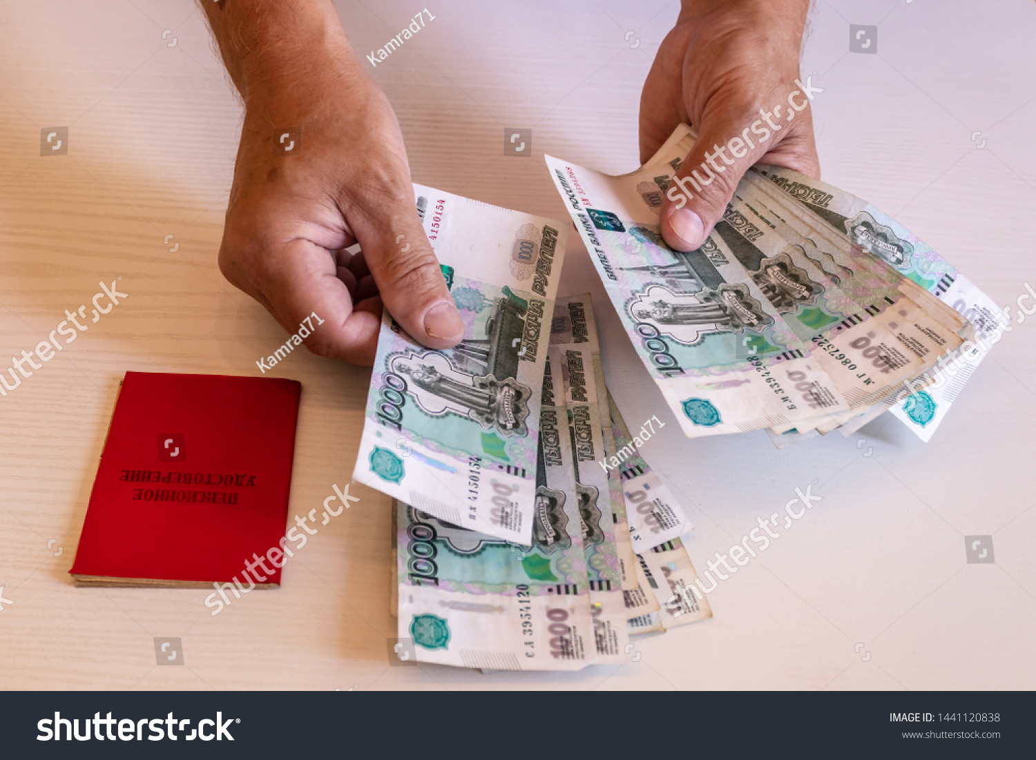 the hands of the pensioner considers bills in 1000 rubles, a pension certificate. The inscription on the certificate: 'pension certificate' #1441120838