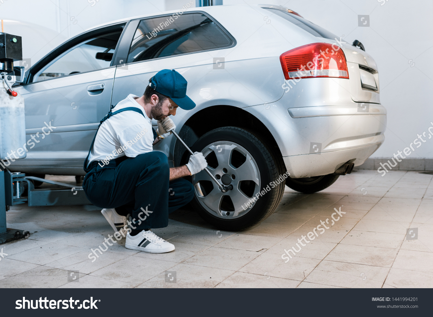 bearded car mechanic in uniform changing car tire in car service  #1441994201