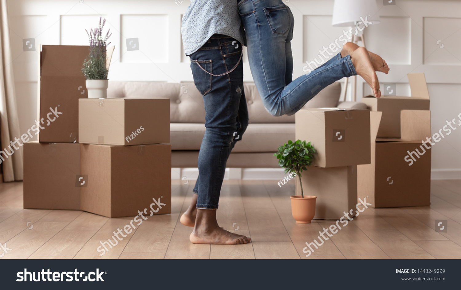 Close up young husband in jeans lift wife surrounded by cardboard boxes excited to move in new flat, happy african American couple have fun hug feel euphoric relocating together to own house #1443249299