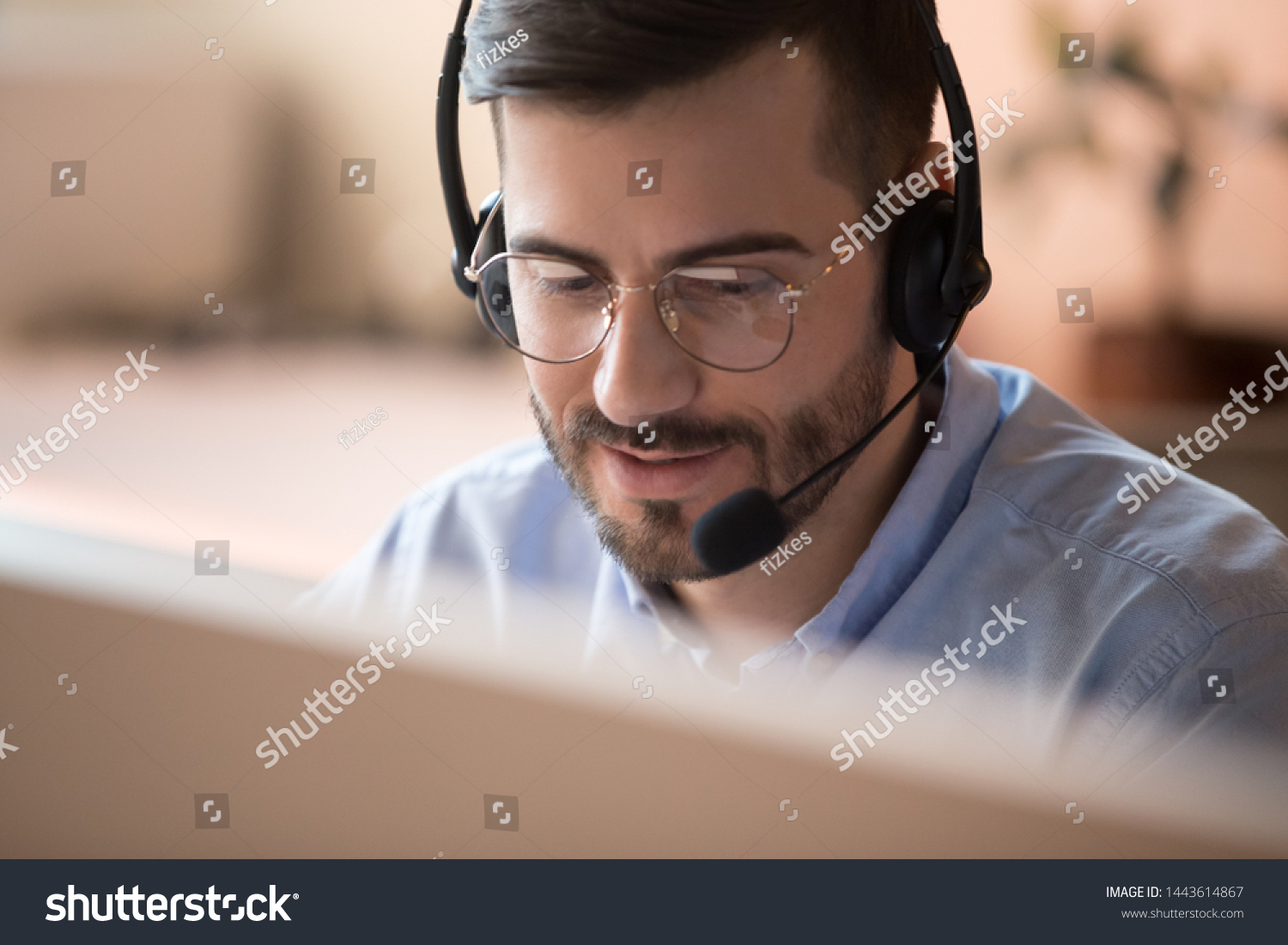 Focused businessman telemarketer telesales agent wear wireless headset make conference video call talk consult online client on computer, male helpline operator work in customer care support office #1443614867