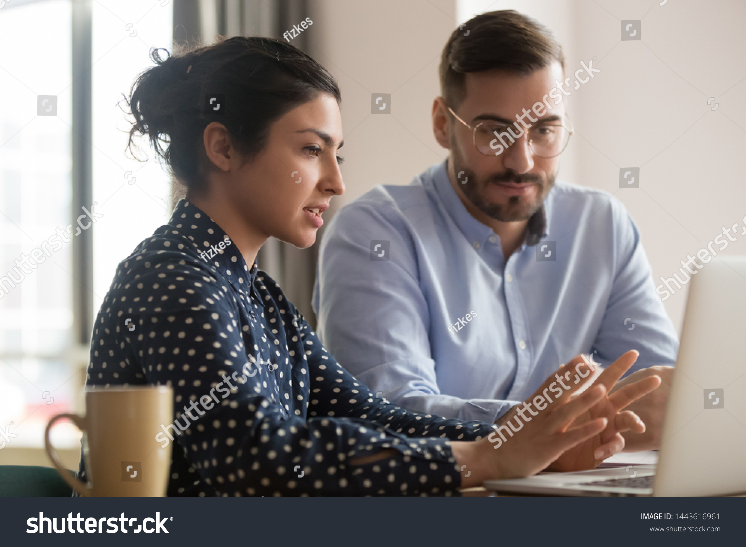 Focused male intern listening to serious indian business woman mentor teacher explaining online strategy looking at laptop computer teach trainee training new worker learning new skill at workplace #1443616961