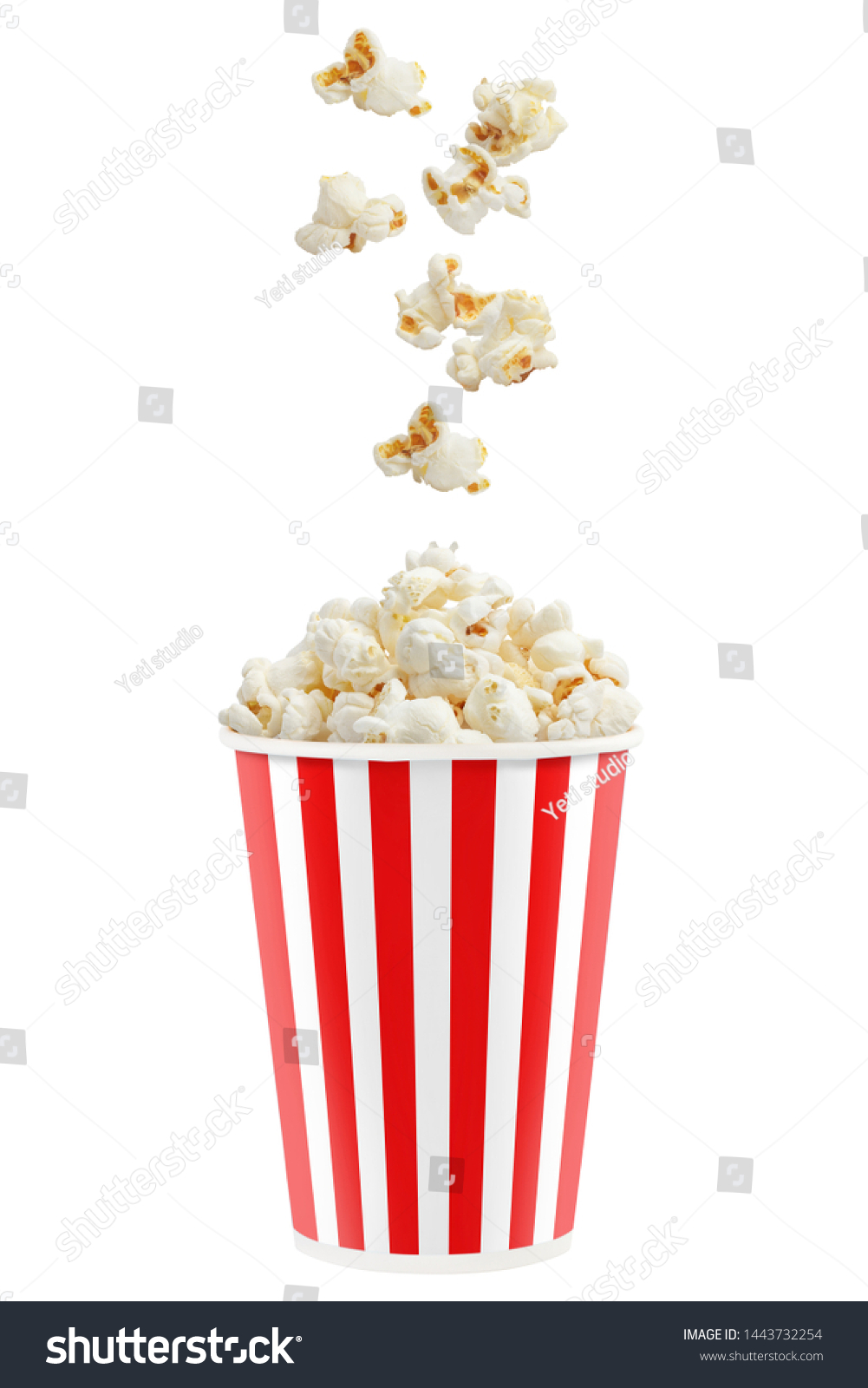 Popcorn falling into a red striped paper cup, isolated on white background #1443732254