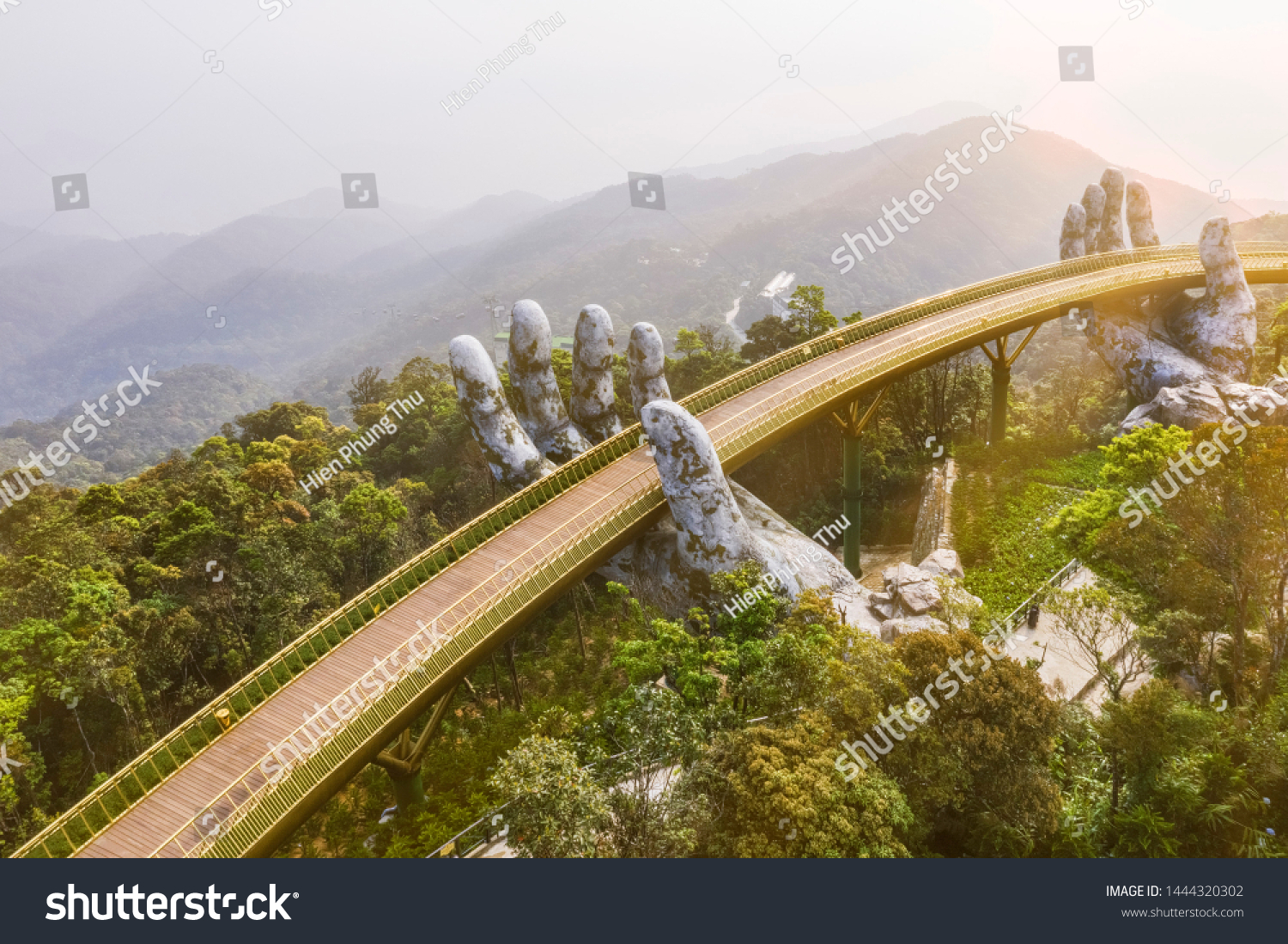"""Top aerial view of the famous Golden Bridge is lifted by two giant hands in the tourist resort on Ba Na Hill in Da Nang, Vietnam. """" Cau Vang"""" is a favorite destination for tourists #1444320302"""
