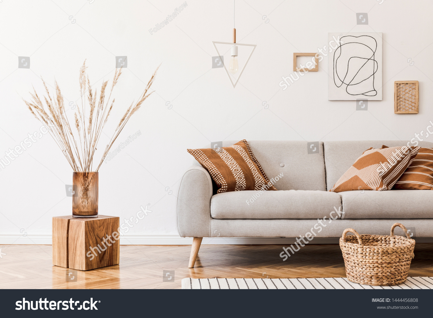 Modern boho interior of living room at cozy apartment with gray sofa, honey yellow pillows and plaid, mock up paintings, rattan basket and design personal accessories. Stylish home decor. Template. #1444456808