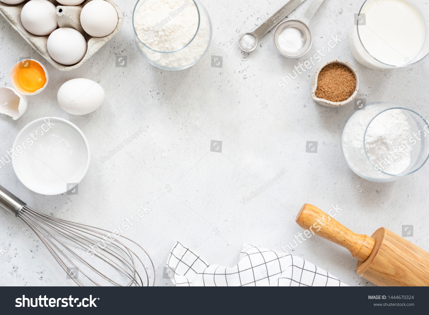 Frame of baking and cooking bread pastry or cake ingredients, flour sugar milk eggs and coconut butter on bright grey background with copy space for text, flat lay #1444670324