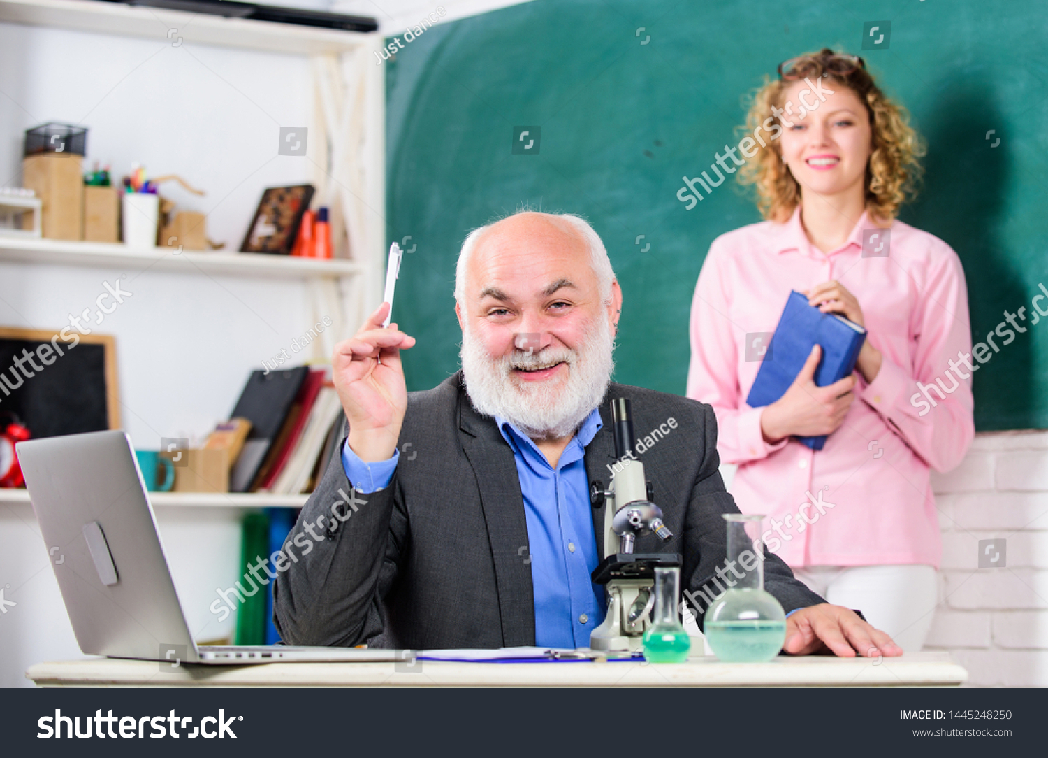 Biological research. Teacher and girl with notepad near chalkboard. College university education. Biologist or chemist with microscope teaching student biology. Biology science. Study biology. #1445248250