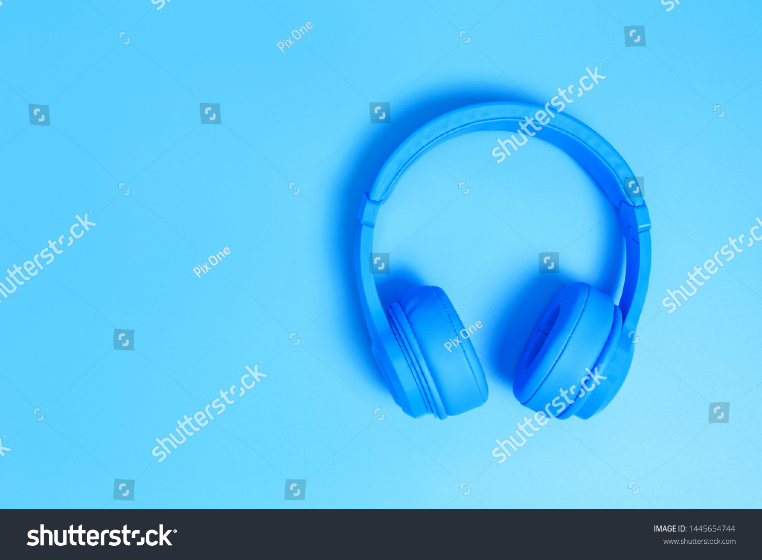a headphones, Top view of headphones on blue background. Minimalist photo of earphones with copy space. blue dj headphones, Top view blue headphones on blue background. Above view of dj head phones. #1445654744