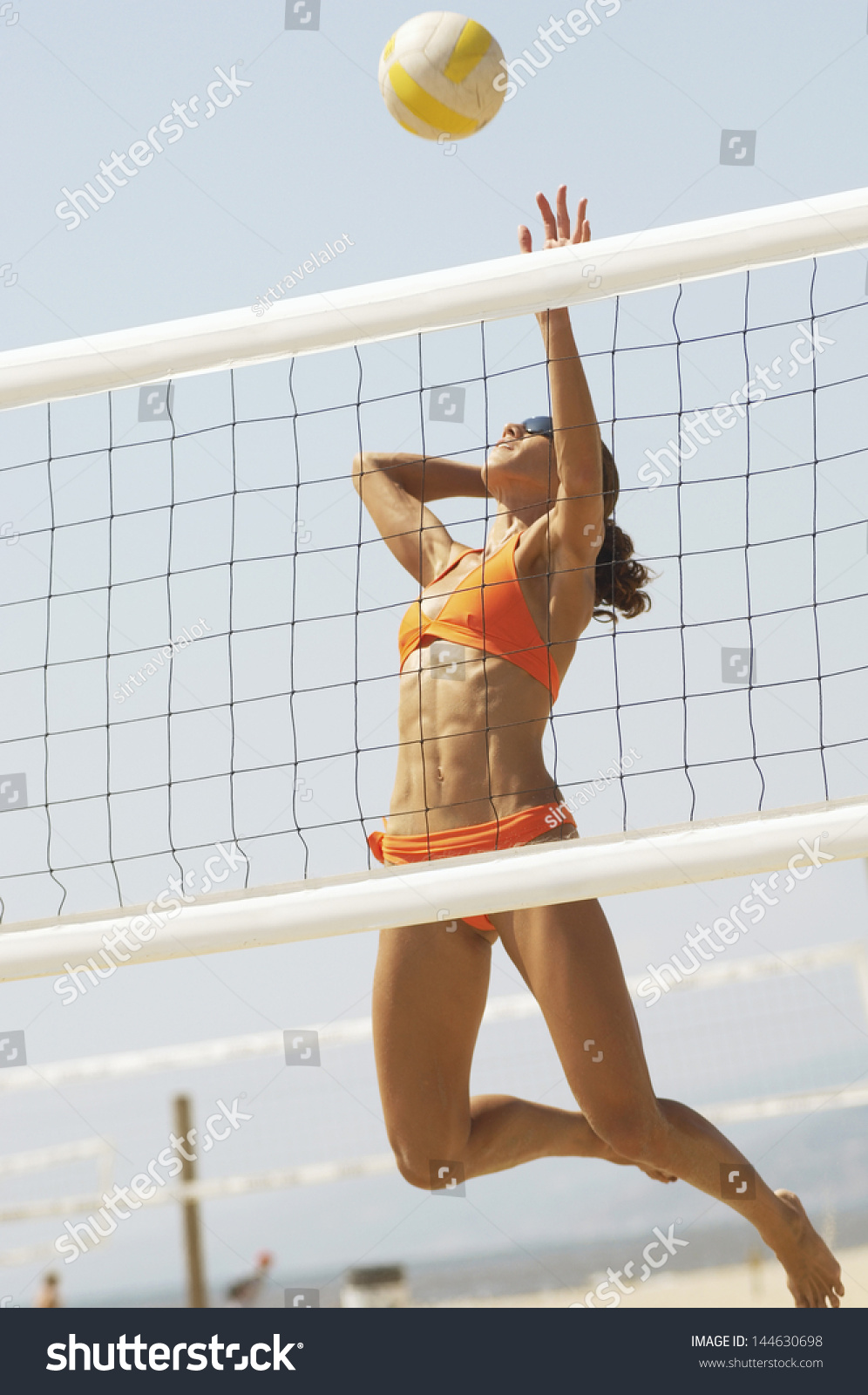 female beach volleyball player jumping spike stock photo