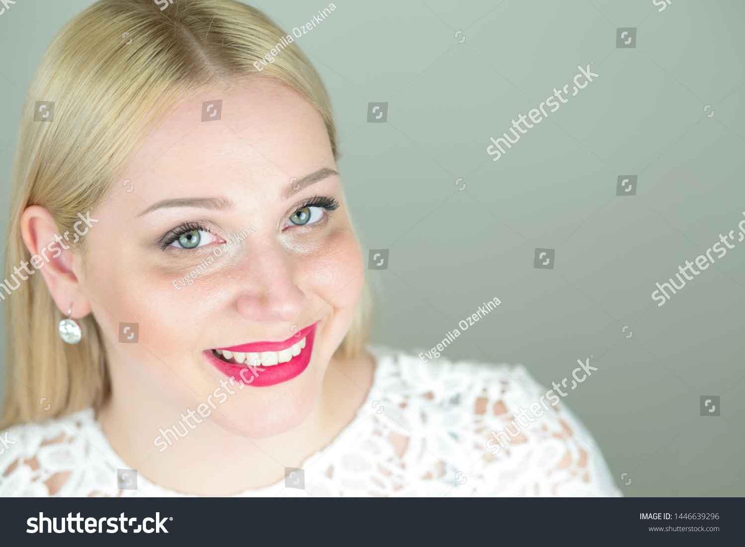 Positive attractive beautiful young blonde woman with long hair close-up smiling in a white openwork dress.  a close up of the head of a blonde with a bright make-up isolated on a gray studio backgrou