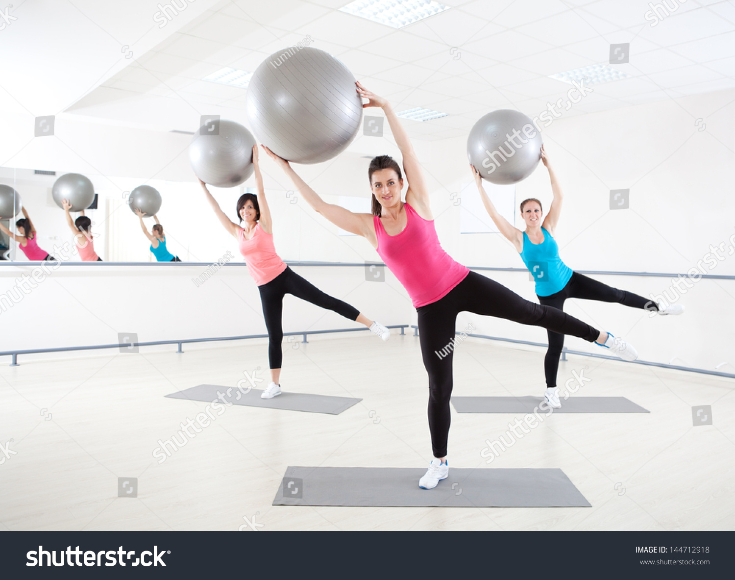 Young women doing exercise pilates ball stock photo for Gimnasio pilates