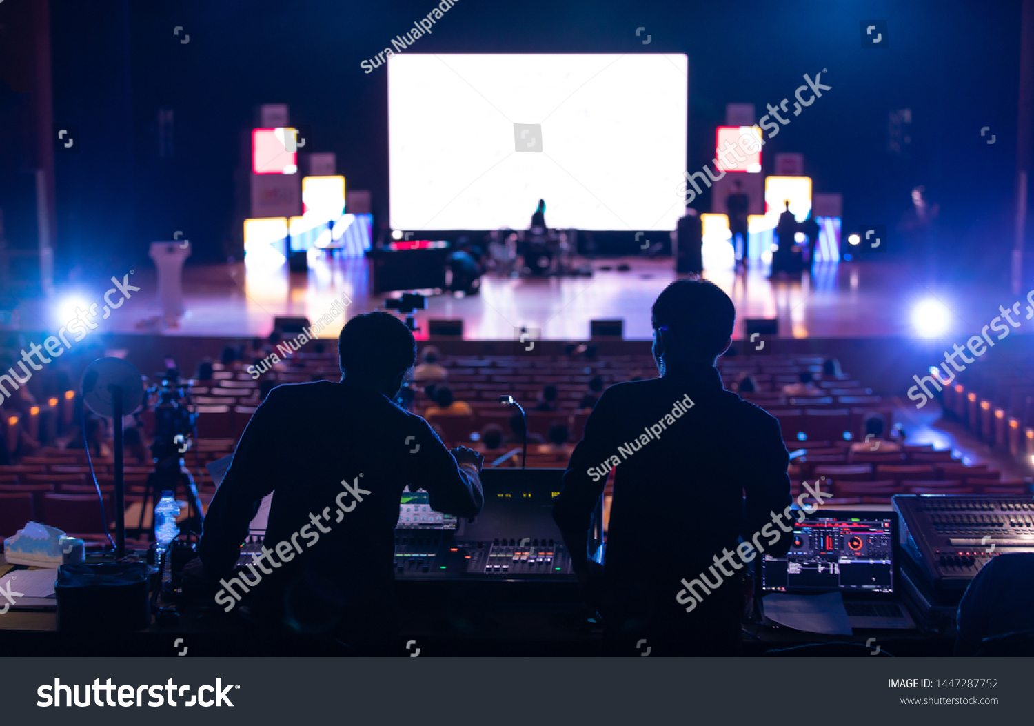 Blur image of sound engineer backstage crew team working to setting and preparing production for show events or music concert stage with blurry white screen in background. #1447287752