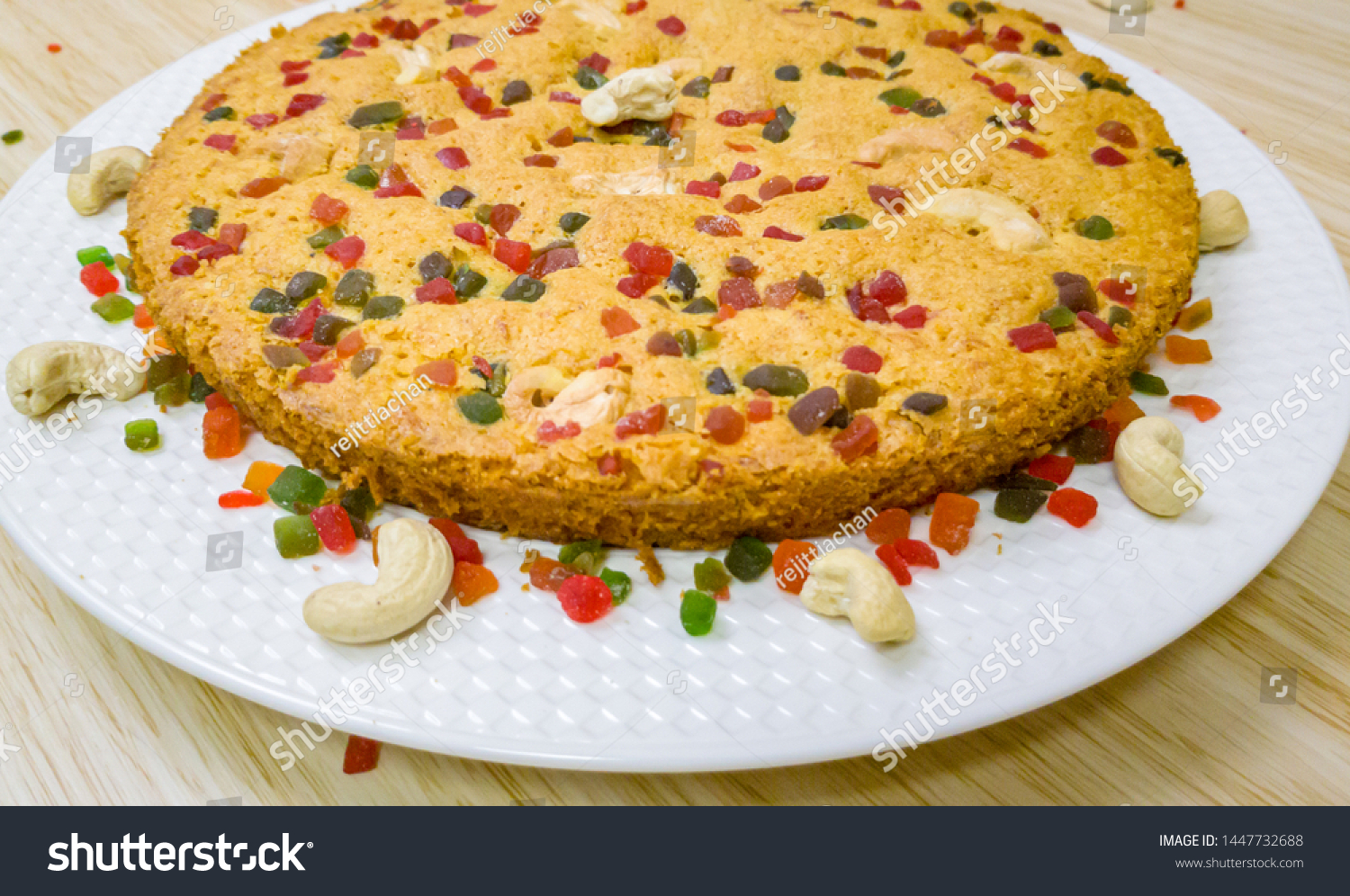 A perfectly baked carrot cake garnished with cashew and tutti frutti.