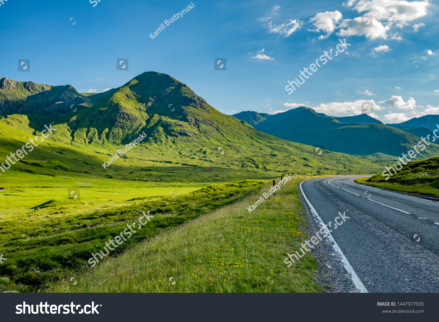Road turning right with green hills and blue sky with white clouds, Highlands, Scotland, United Kingdom