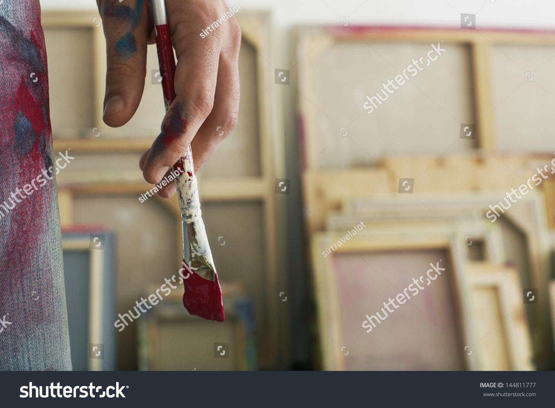 Closeup of an artist holding paintbrush #144811777