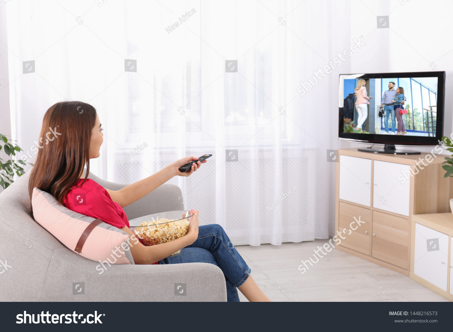 Young Woman Watching Tv On Sofa Stock Photo (Edit Now) 1448216573