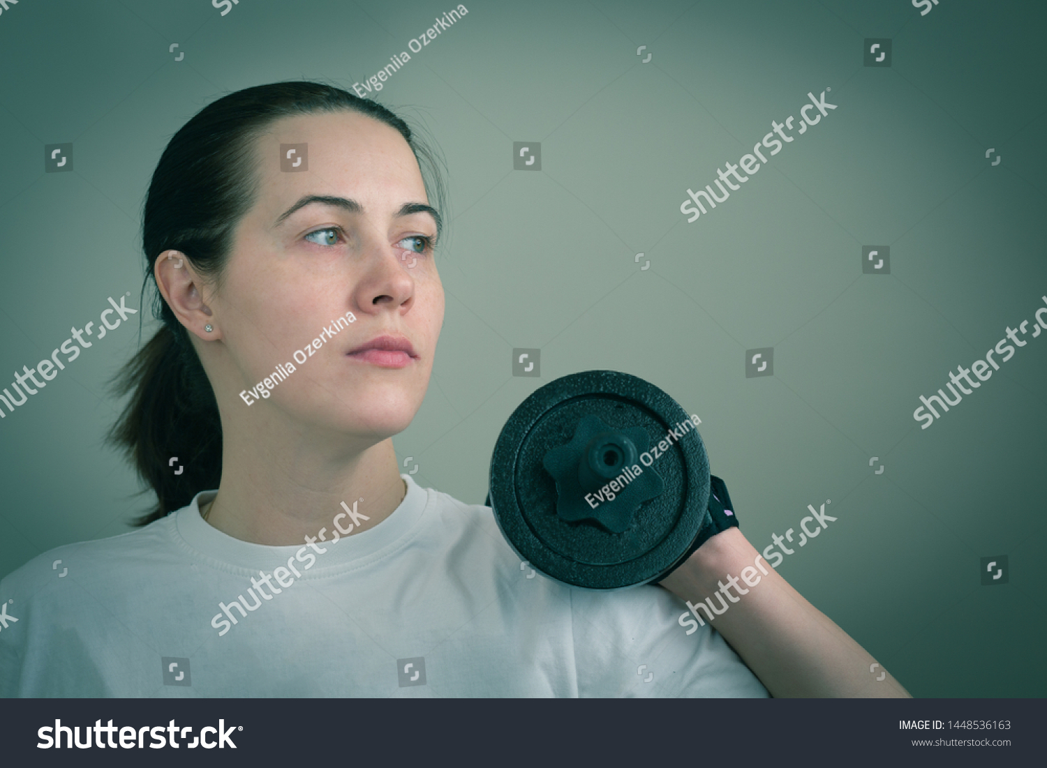 Portrait of a white caucasian woman holding heavy iron dumbbells close-up. Toned image in blue. Concept of home fitness due  coronavirus quarantine