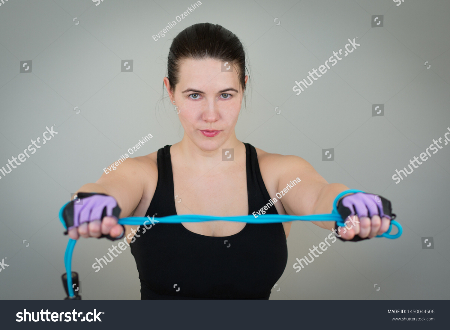 beautiful white caucasian girl in a black T-shirt on fitness holding a jump rope on outstretched arms. Isolated on gray studio background