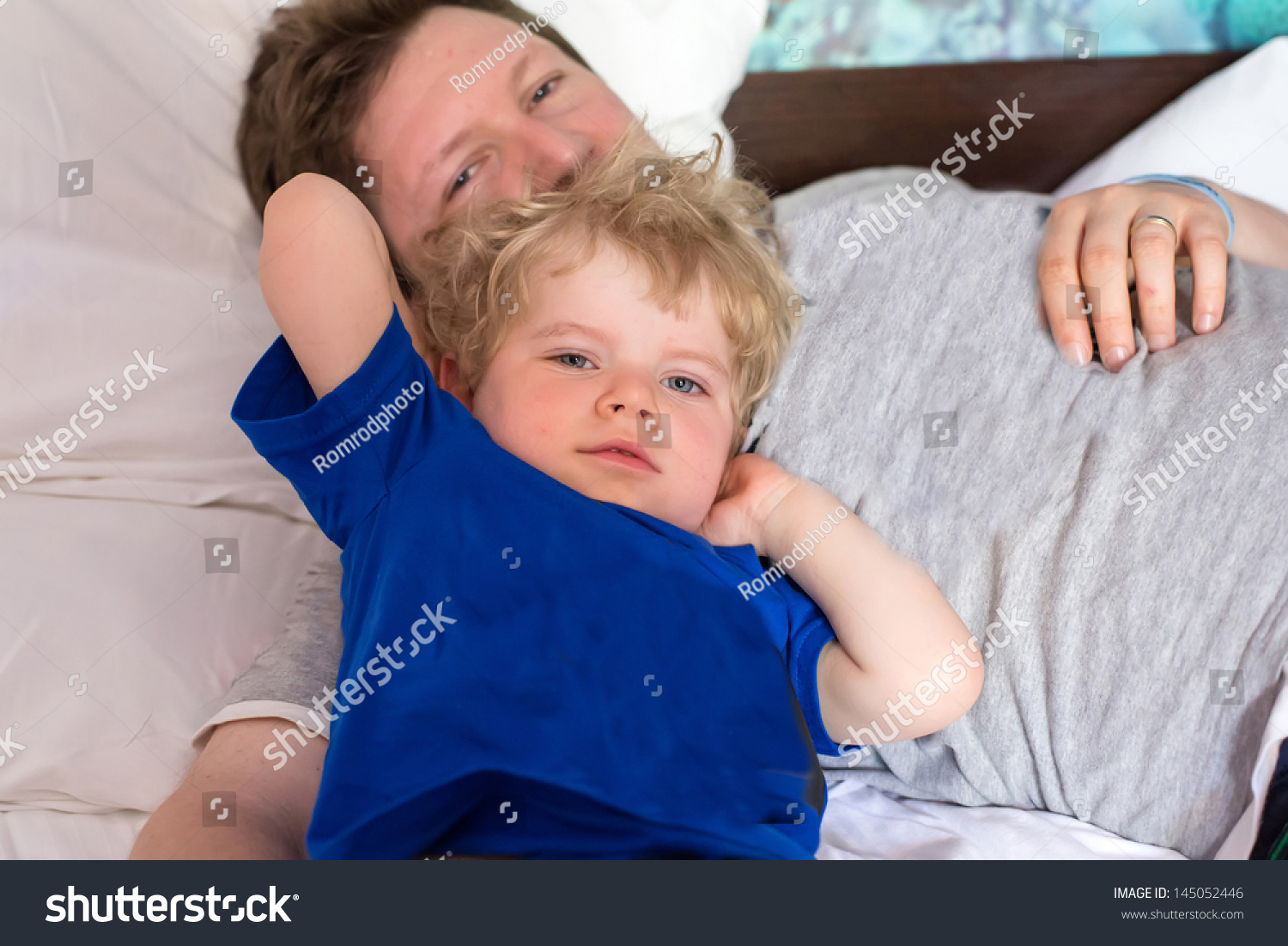 Young Father And Little Toddler Boy Having Fun Together In Bed