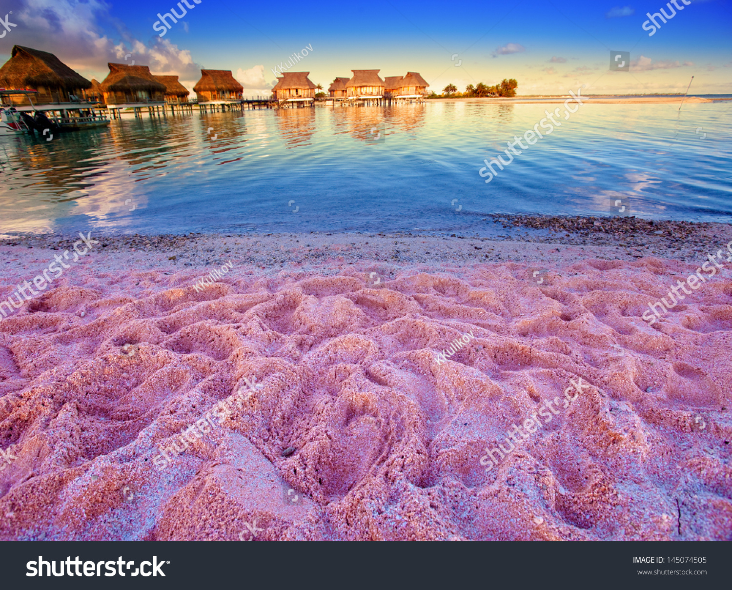 Beach With Pink Sand And Lodges On Water