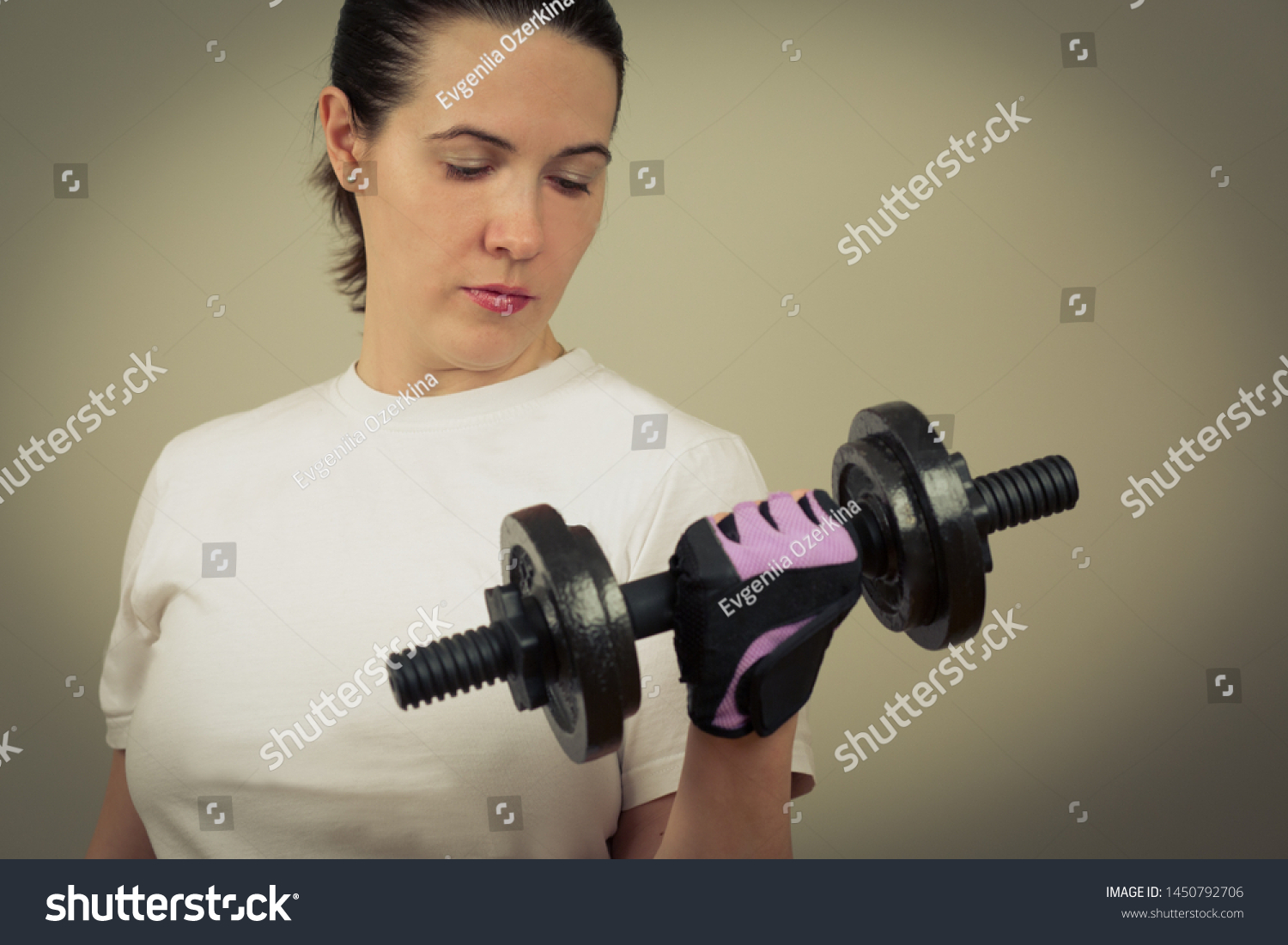 Portrait of a white caucasian woman holding heavy iron dumbbells close-up. Toned image in green gray