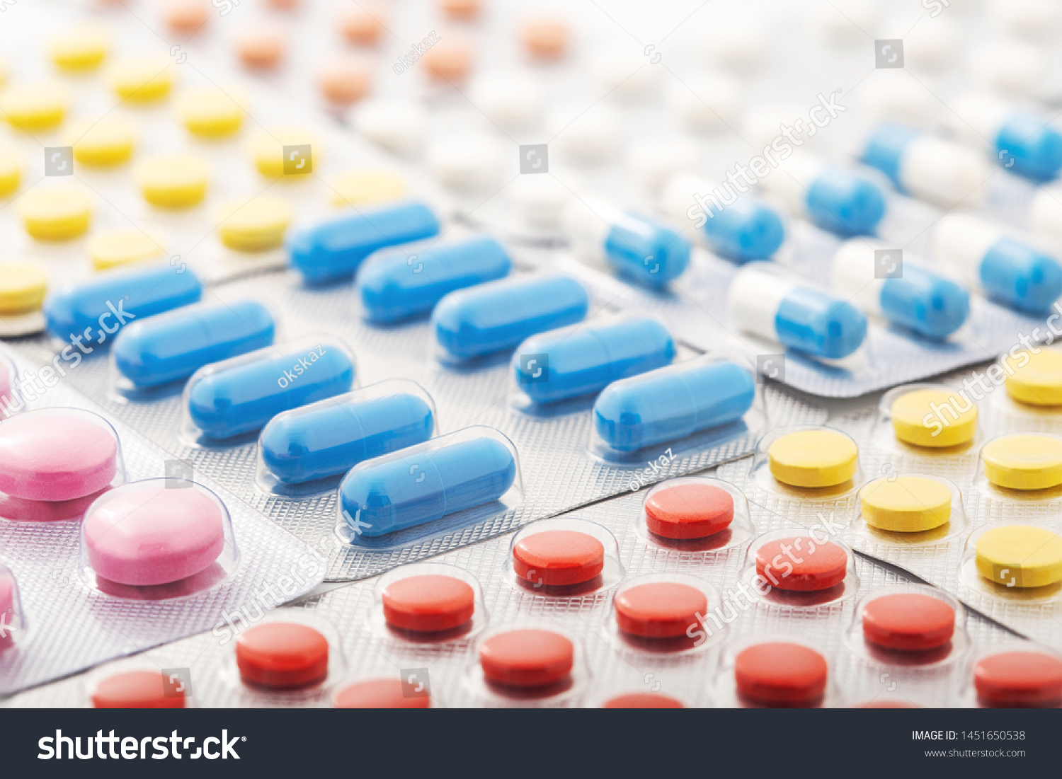 Heap of medical pills in white, blue and other colors. Pills in plastic package. Concept of healthcare and medicine. #1451650538