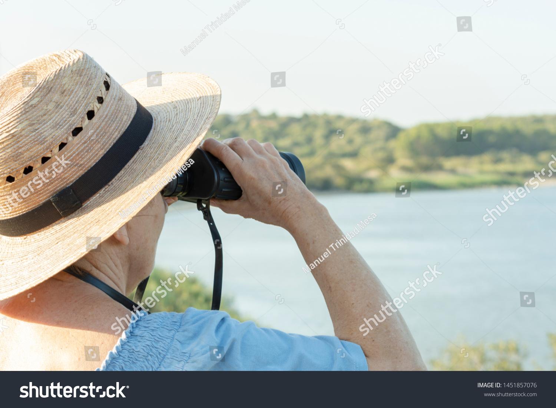 Mujer observa las aves del lago con binoculares
