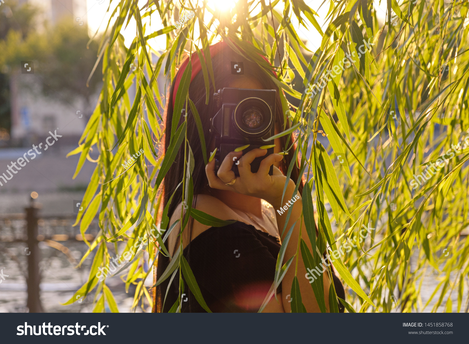 Asian Girl with camera in the park in sunset time. Brunette girl with film camera in the vintage colored image in front of willow branches