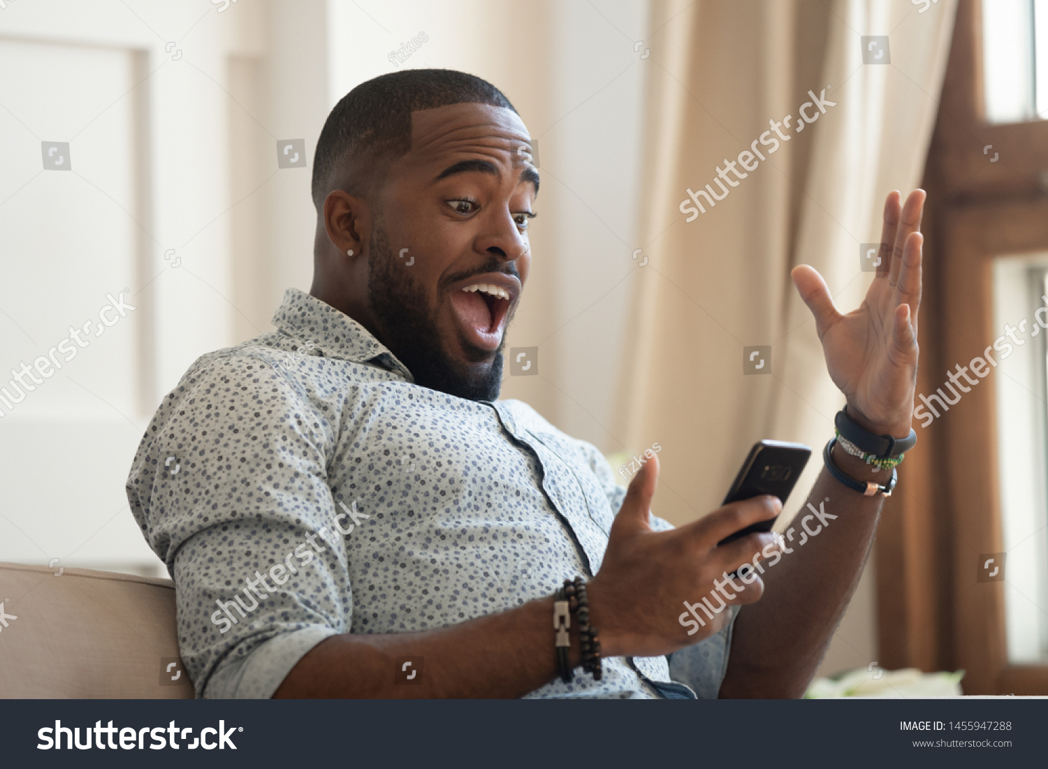 Surprised happy african man holding phone looking at cellphone read good news in sms sit on sofa, amazed black guy winner excited by mobile app win scream with joy celebrate victory success at home #1455947288